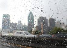 Gocce di pioggia nella finestra di automobile sulla strada principale di Bangkok immagine stock