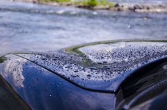 Gocce di pioggia o goccioline di acqua sulla superficie dell'automobile fotografia stock