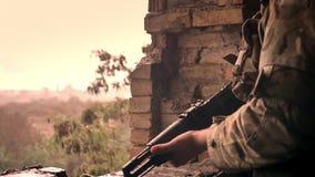 Gocce di pioggia pesanti del primo piano sul soldato in cammuffamento, stando, guardando arma e guardando avanti diritto potente  archivi video