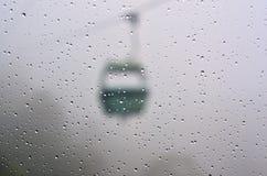Gocce di pioggia su un vetro di finestra di una gondola della teleferica Immagine Stock Libera da Diritti
