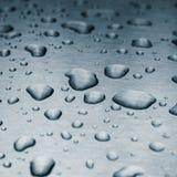 Gocce di pioggia su una superficie di metallo spazzolata fotografia stock libera da diritti