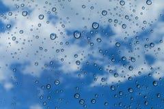 Gocce di pioggia sul fondo del cielo blu e di vetro/sulle gocce su vetro fotografie stock libere da diritti