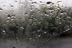 Gocce di pioggia sul primo piano di vetro fotografie stock libere da diritti