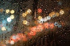 Gocce di pioggia sul vetro, contro lo sfondo della via di notte Fotografie Stock Libere da Diritti