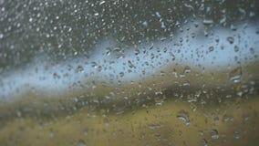 Gocce di pioggia sul vetro dell'automobile stock footage