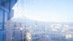 Gocce di pioggia sul vetro di finestra con la montagna di Fuji Fotografia Stock