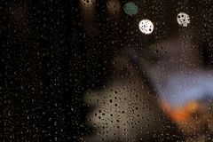 Gocce di pioggia sulla finestra alla notte fotografia stock