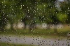 Gocce di pioggia sulla finestra di automobile con luce solare, vetro bagnato, giorno piovoso fotografie stock libere da diritti
