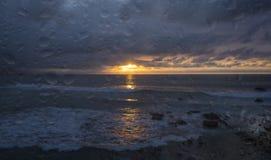 Gocce di pioggia sulla finestra con il bello tramonto sul mare Immagini Stock
