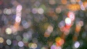 Gocce di pioggia sulla finestra con le luci del bokeh della via stock footage