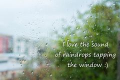 """Gocce di pioggia sulla finestra con testo """"amo il suono delle gocce di pioggia che spillano le finestre """" fotografia stock libera da diritti"""
