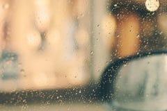 Gocce di pioggia sulla finestra di automobile con i citylights fuori fotografie stock