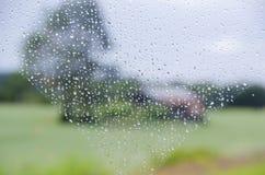 Gocce di pioggia sulla finestra e sul paesaggio rurale confuso Fotografia Stock