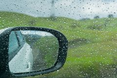 Gocce di pioggia sulla finestra e sullo specchietto retrovisore esterno; prati verdi vaghi nei precedenti Fotografie Stock Libere da Diritti