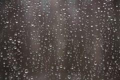 Gocce di pioggia sulla finestra sui precedenti scuri Modello naturale Caduta Fotografia Stock Libera da Diritti