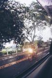 Gocce di pioggia sulla pioggia persistente del retrovisore dell'automobile fuori Immagini Stock