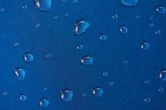 Gocce di pioggia sulla superficie di metallo blu immagini stock