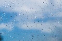 Gocce di pioggia sullo schermo della finestra con gli ambiti di provenienza del cielo blu Fotografie Stock