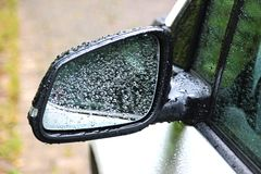 Gocce di pioggia sullo specchio di un'automobile fotografia stock libera da diritti