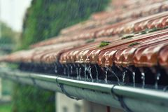 Gocce di scorrimento dell'acqua nella gronda Immagine Stock