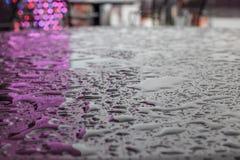 Gocce o piccole pozze di acqua dopo la pioggia su una superficie opaca regolare di colore scuro, riflettente le luci di illuminaz fotografia stock
