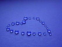 Gocce sotto forma di cuore su un fondo blu Fotografia Stock