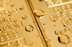 Gocce su un oro Immagine Stock