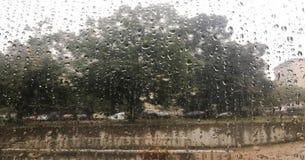 Gocce sulla bella luce della finestra, vetro bagnato Gocce di pioggia sul vetro, paesaggio confuso su fondo immagini stock