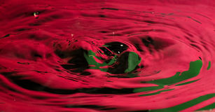 Goccia chiara e spruzzata dell'acqua rossa Fotografia Stock