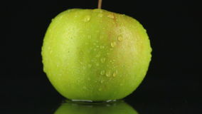 Goccia degli scorrimenti dell'acqua giù la pelle di una mela verde stock footage