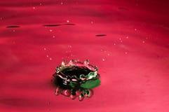 Goccia dell'acqua rossa e reticolo della spruzzata fotografia stock
