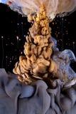 Goccia dell'inchiostro di colore liquido oro, viola, gocce volanti Fotografia Stock Libera da Diritti