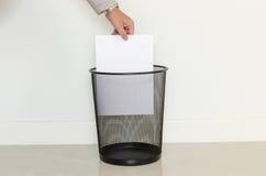 Goccia dell'uomo di affari una carta inutile dentro ai rifiuti immagini stock