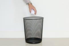 Goccia dell'uomo di affari una carta inutile dentro ai rifiuti Immagini Stock Libere da Diritti