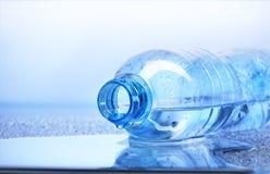 Goccia di acqua che cade dalla bottiglia di plastica con la riflessione Fotografia Stock