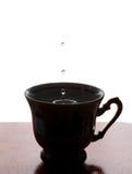 Goccia di acqua Tazza di tè con spruzzata Priorità bassa bianca Copi lo spazio fuoco molle, macro vista Fotografia Stock
