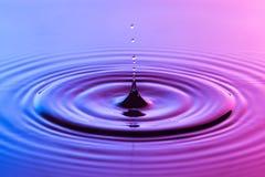 Goccia di acqua vicina su con il blu colourful delle ondulazioni concentriche e la p Fotografia Stock