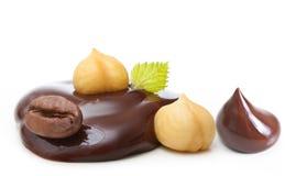 Goccia di cioccolato con i dadi ed il chicco di caffè Immagini Stock