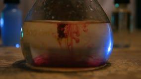 Goccia di colore che cade in acqua che crea una diffusione di colore video d archivio