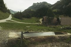 Goccia di legno della fontana davanti alle tracce ed alle alpi di escursione Fotografia Stock Libera da Diritti