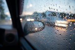 Goccia di pioggia sulla finestra con la traccia leggera Fuoco selettivo immagine stock