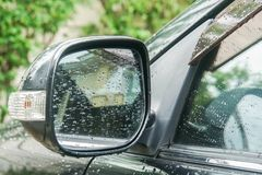 Goccia di pioggia sullo specchietto retrovisore esterno del parcheggio nero all'aperto immagine stock libera da diritti