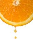 Goccia di spremuta che cade dalla metà arancione isolata Immagine Stock Libera da Diritti