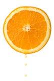 Goccia di spremuta che cade dalla metà arancione isolata Immagine Stock