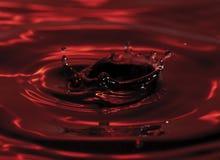 Goccia e spruzzata dell'acqua rossa Fotografia Stock Libera da Diritti