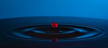 Goccia rossa di acqua e dei cerchi sull'acqua su fondo blu immagine stock