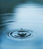 Gocciolina che cade in acqua blu Fotografie Stock