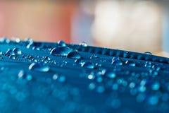 Goccioline dell'acqua piovana su tessuto impermeabile blu fotografia stock