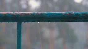 Goccioline di acqua che gocciolano con le finestre, i balconi o l'inferriata contro lo sfondo della via in cui c'è pioggia video d archivio