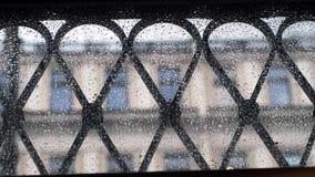Goccioline piovose sulla finestra durante la pioggia sul fondo vago della via Immagini Stock Libere da Diritti